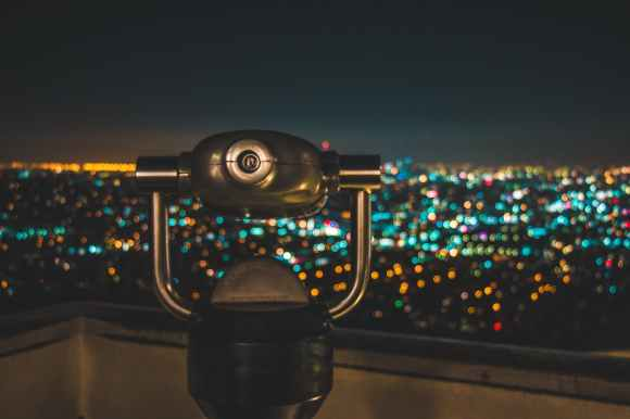 black binocular facing lighted city at nighttime