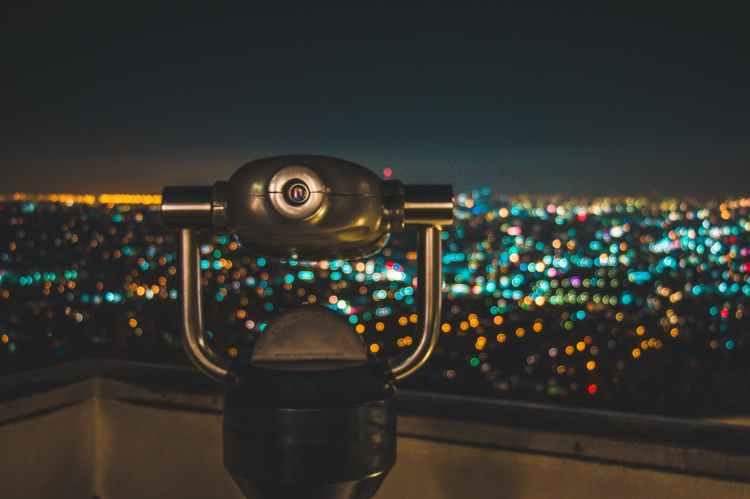 black binocular facing lighted city at nighttime